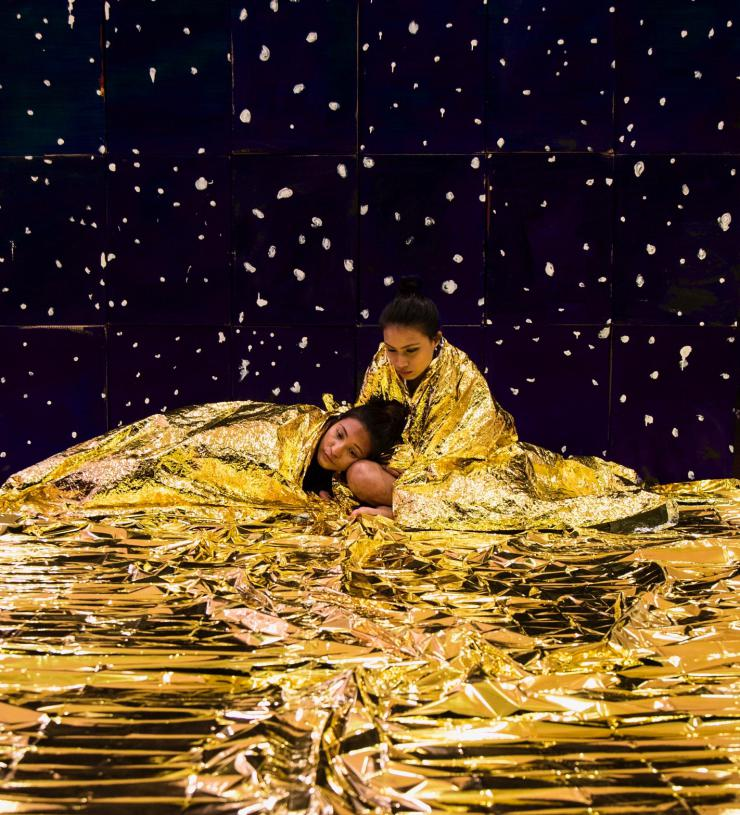 Two actors on stage together in a gold foil blanket
