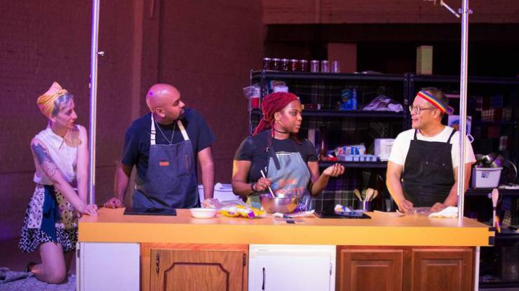 four performers talking in a kitchen