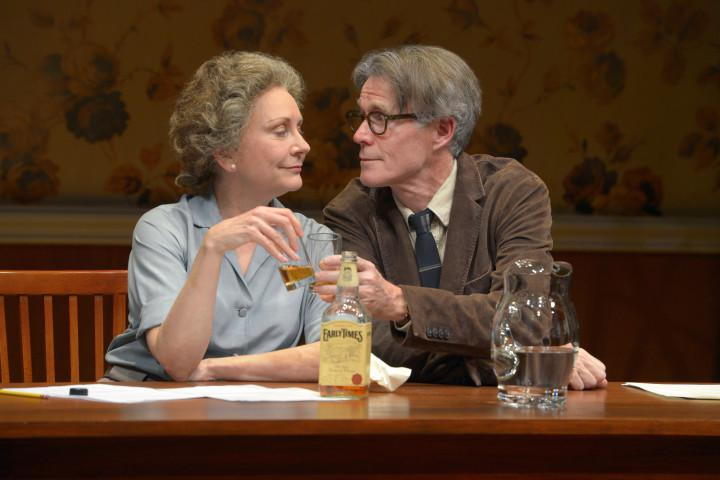 An older man and women on stage drinking scotch.