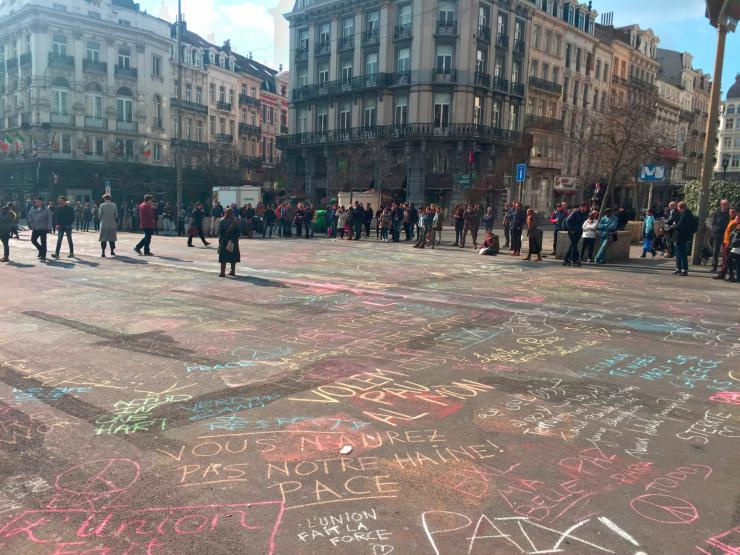 a square in Brussels full of political messages written in chalk