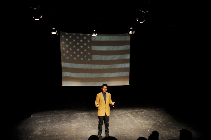 lone actor on stage in front of projection of American flag