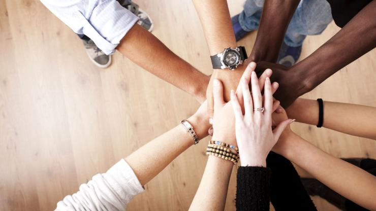 nine hands of various skin tones all together in a huddle of solidarity