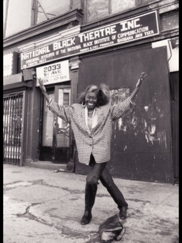A women with her hands in the air in front of a theater