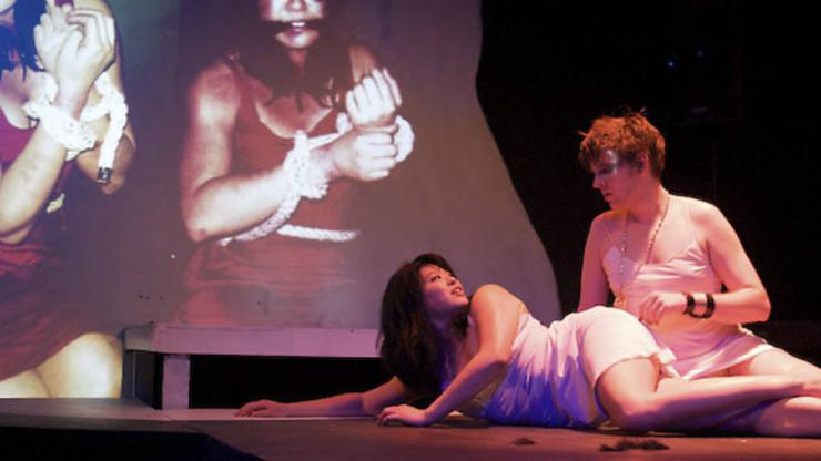 two actors in slips laying onstage with projection behind them