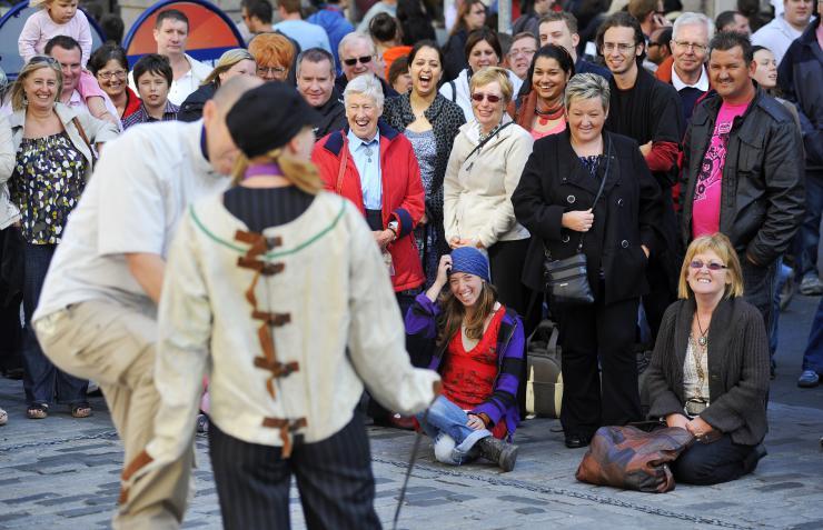 Crowd of people watching a pair of street performers