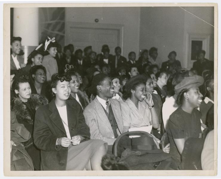 black and white photo of African Americans sitting and smiling