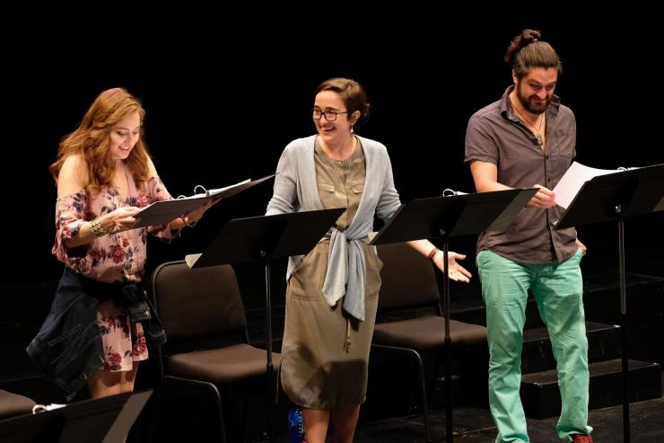 Three actors on stage at music stands