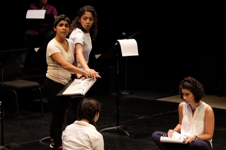 Two women stand at music stands and two sit on a stage, all with scripts in hand.