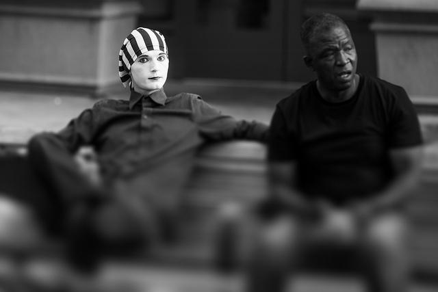 a mime and man sit on a bench