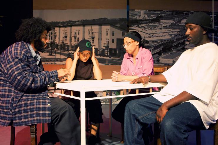 Four performers sit around a table