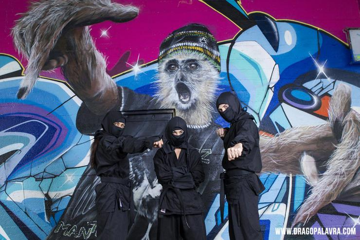three performers in ninja costumes pose in front of a graffiti wall
