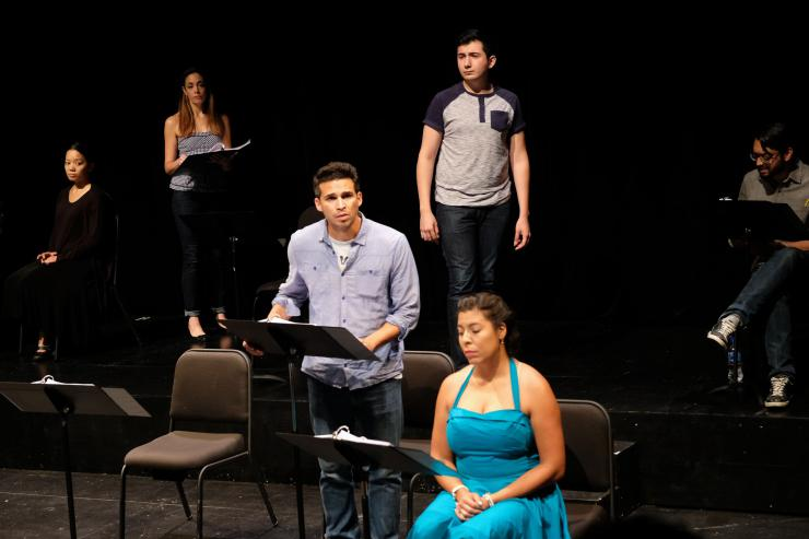 Six actors on stage at music stands.