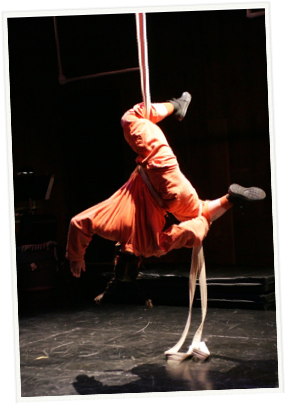 person hanging from an aerial silk