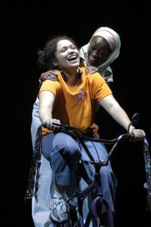 Two women on a bicycle on stage