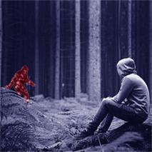 a boy sitting in forest looking at a monster