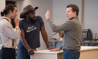 director in a rehearsal room talking to two actors