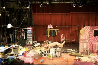 naked performer doing an acrobatic move in the middle of a crowded set