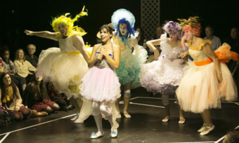 Several actors stand and pose wearing colorful tutus, wigs, and makeup as an audience watches.