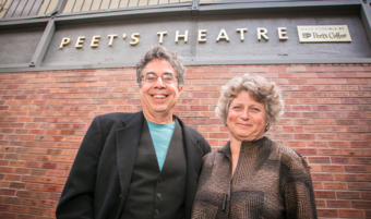 Two people smiling in front of a theatre