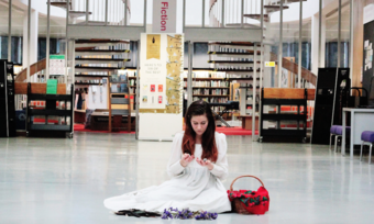 performer in white dress sits in the fiction section of the library