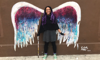 a person in front of a colorful angel wings mural