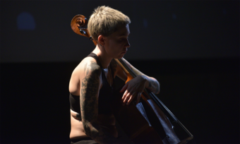 close up of an actor playing the cello