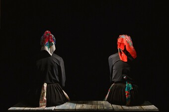 Two actors in traditional Roma women clothing with their backs to us.