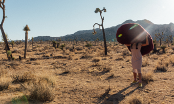 a person with a large bean bag over their head standing alone in the desert