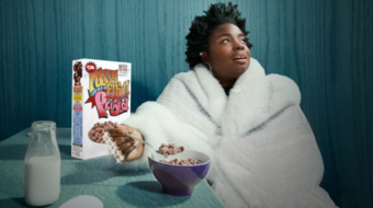 a person sitting in a bathrobe eating breakfast cereal