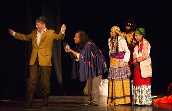 Five actors on stage dressed in Roma clothes from the 1940's.