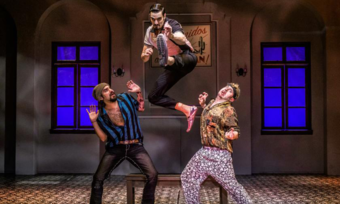 three actors onstage, one jumping in the air.