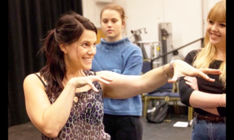 Intimacy Director Tonia Sina expressing an idea with her arms and hands in a rehearsal with two actors