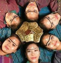 six performers lying down, their faces in a circular pattern.