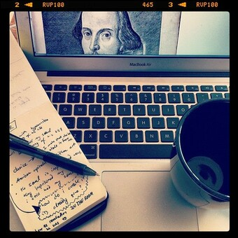 photo of laptop with notebook, mug, and an image of Shakespeare