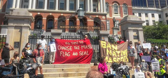 "A group of people in front of the Massachusetts State House holding a banner that reads ""It's time to change the mass flag and seal"" and ""ban the native mascots""."