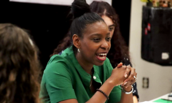 tamilla woodard in a green blouse seated and talking