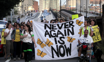 "a group marching outside with a banner that reads ""NEVER AGAIN IS NOW"""