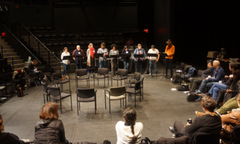 a large group sitting in a circle watching a staged reading