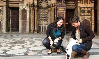 two people kneel in front of ornate architecture, petting a black and white cat