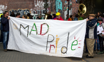 "a group of people holding a banner saying ""MAD Pride"""