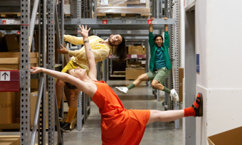 three people posing for a photo in an ikea warehouse