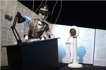 Puppet is standing behind a desk made to scale with tiny lamp and white phone. Newspaper clippings compose the backdrop.