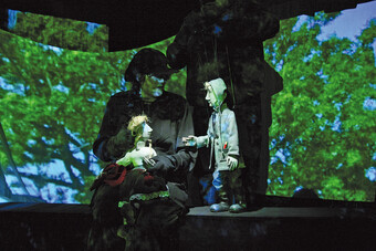 Image of two puppeteers on stage using puppets in front of a digital created forest backdrop.