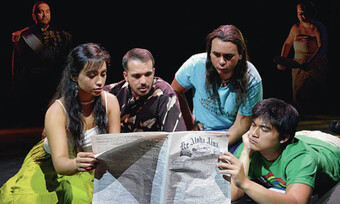 actors on stage looking at a newspaper.