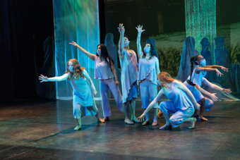 six performers on a stage with watery blue silks
