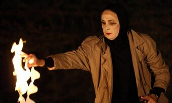 A woman in a black hijab and tan trenchcoat burns a piece of paper cut out in a wavy design.