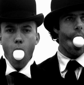 Geoff Sobelle and Trey Lyford in bowler hats blowing bubble gum