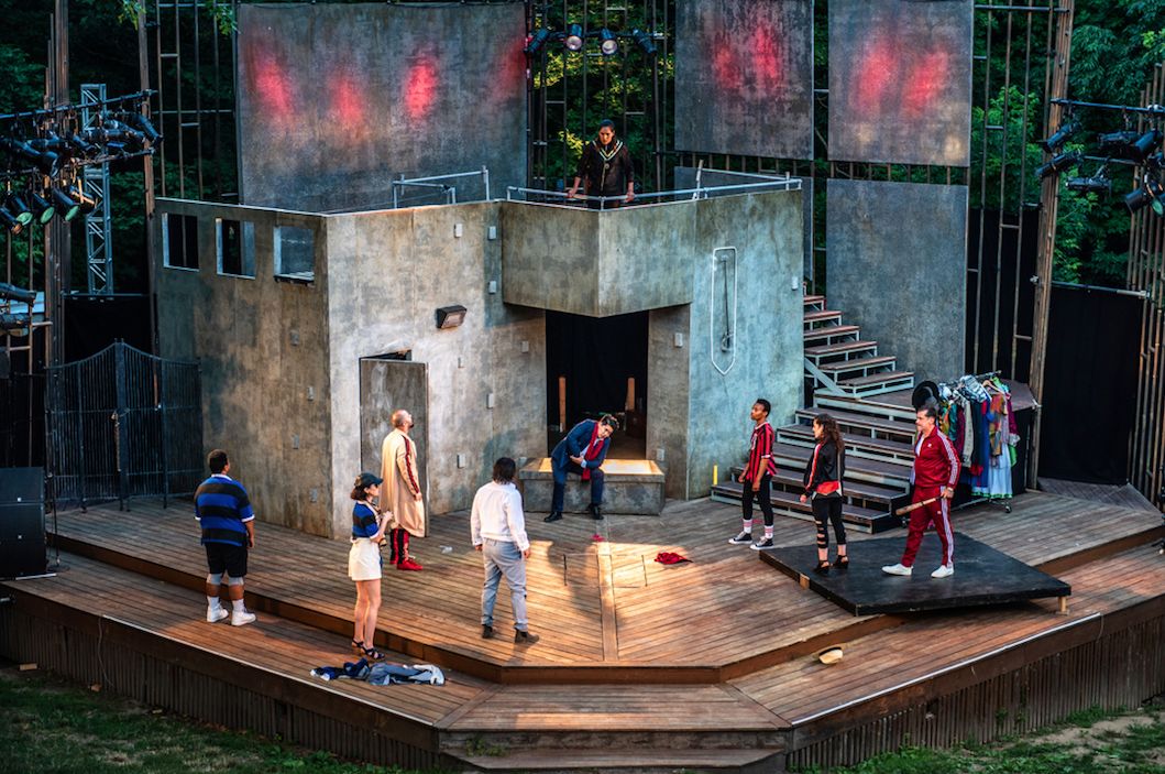 nine actors on an outdoor stage