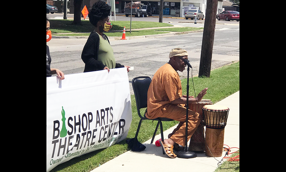 one person seated at a microphone and a drum in front of two people standing with a sign saying Bishop Arts Theatre