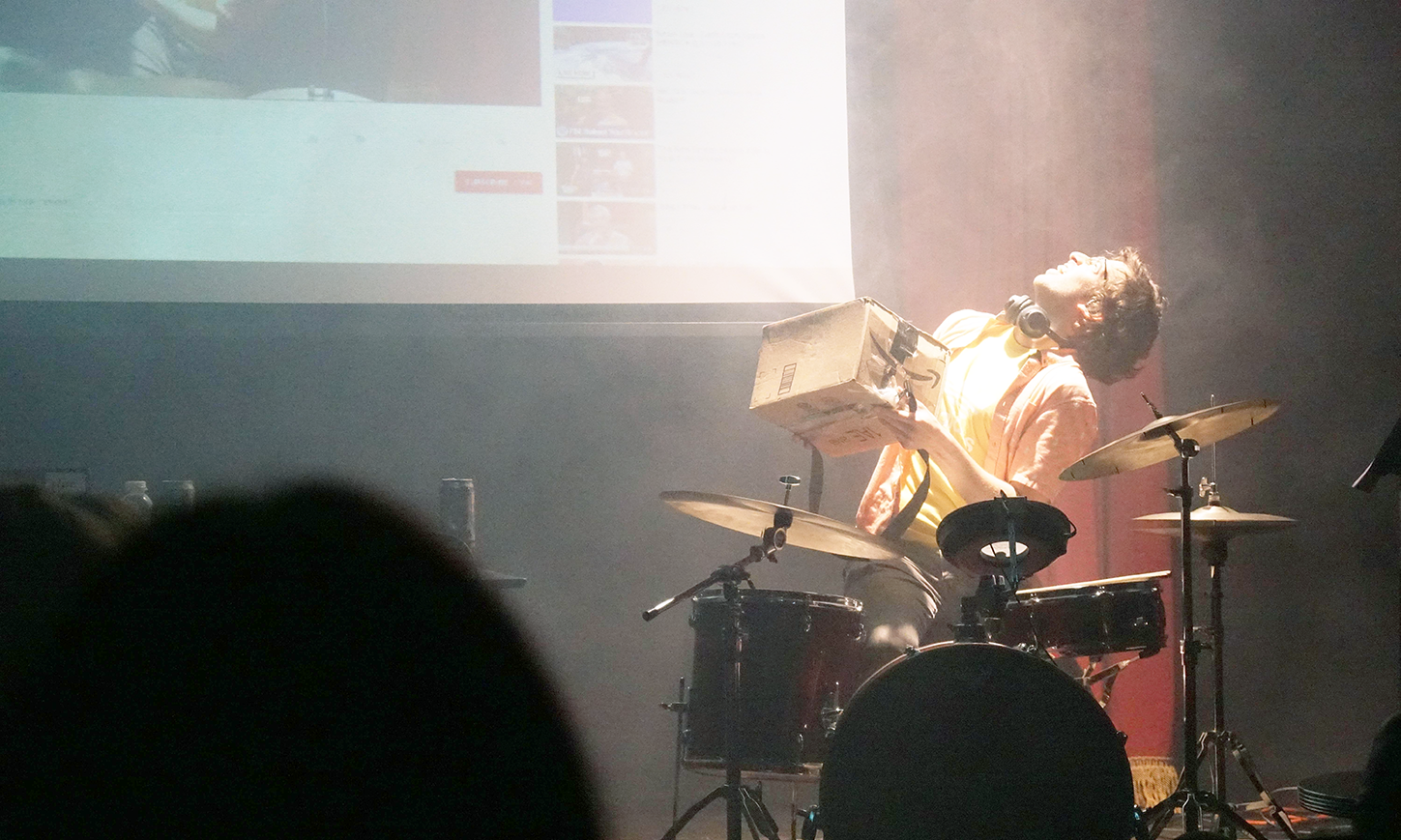 a person seated onstage at a drumset looking up at a projection